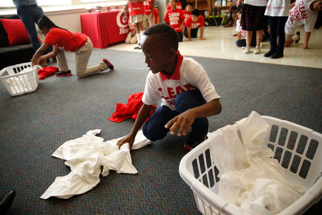 Jaylen Simpson, 8, gathers clothes during a laundry game at a celebration of Conn's HomePlus giving a washer and dryer to clean students' uniforms at Roger Q. Mills Elementary in Dallas on October 20, 2016. (Nathan Hunsinger/The Dallas Morning News)