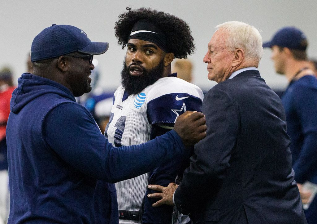 FILE - Cowboys running back Ezekiel Elliott (21) is greeted by team owner Jerry Jones during training camp at The Star in Frisco on Thursday, Aug. 23, 2018. (Ashley Landis/The Dallas Morning News)