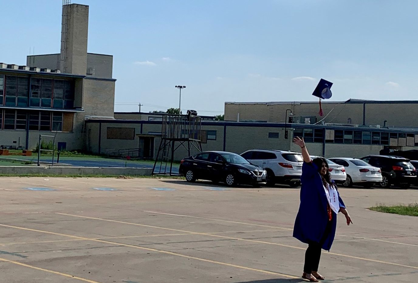 A young woman throws her cap into the air after a socially distanced graduation celebration at Thomas Jefferson High School on May 19, 2020.
