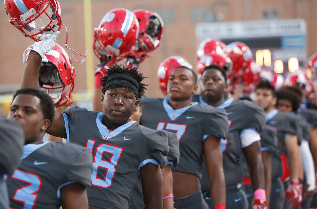 Dallas Skyline defensive back Kev'Veon Sims (18) and his Raiders teammates stand and raise their helmets as they pause for the playing of the national anthem prior to the opening kickoff of their game against Jesuit. The two teams played their District 9-6A football game at Forester Field in Dallas on October 12, 2017. (Steve Hamm/Special Contributor)