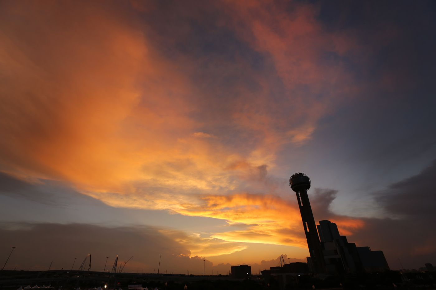 The sun sets behind Reunion Tower as approaching storms loom on the horizon, Friday evening, April 21, 2017. Storms are expected later tonight with a passing cold front.