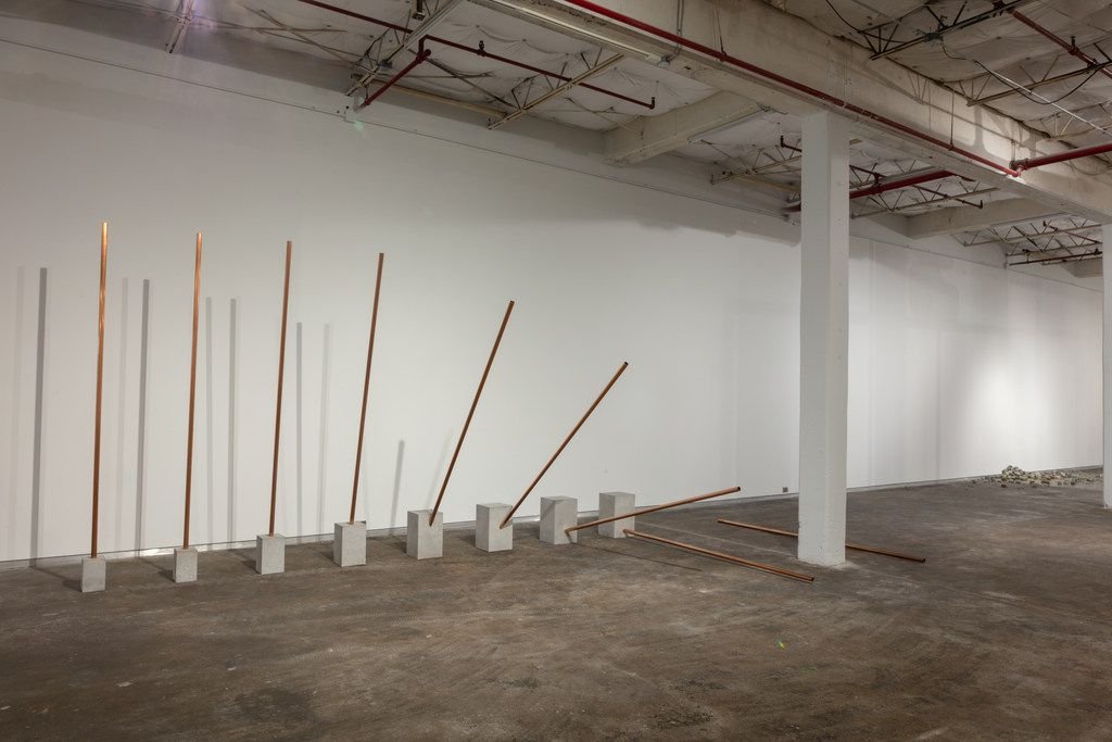 Alicja Kwade's Fall shows a vertical pipe  falling  from vertical to horizontal, appearing to descend a few degrees more each fraction of a second.