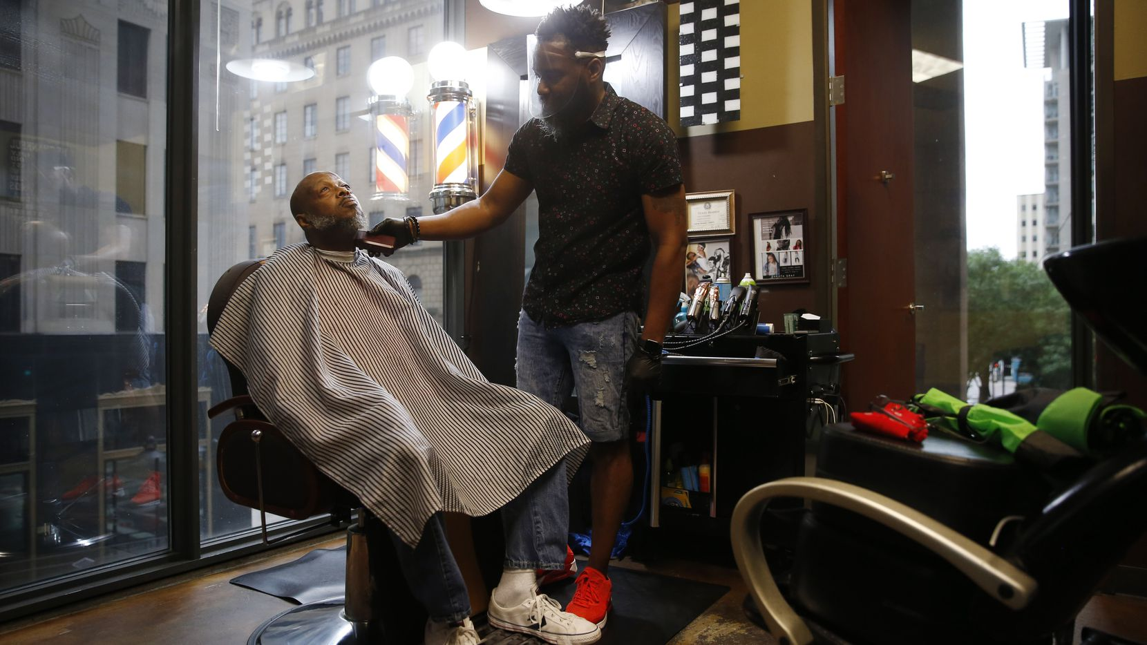 """Carlos Gray, owner of Wow! """"If Looks Could Kill"""" Hair Studio in downtown Dallas, works on the beard of Steven Robinson. Gray was Robinson's first customer Friday, when salons were allowed to reopen after a lengthy closure due to the pandemic."""