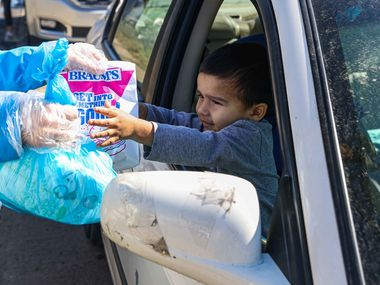 Adolfo Chavarria, 3, receives food aid from volunteer Rachel Harper, 15, at Ledbetter Eagle Ford Community Pantry, housed in Iglesia Bautista El Cavario, on Saturday, Feb. 20, 2021.