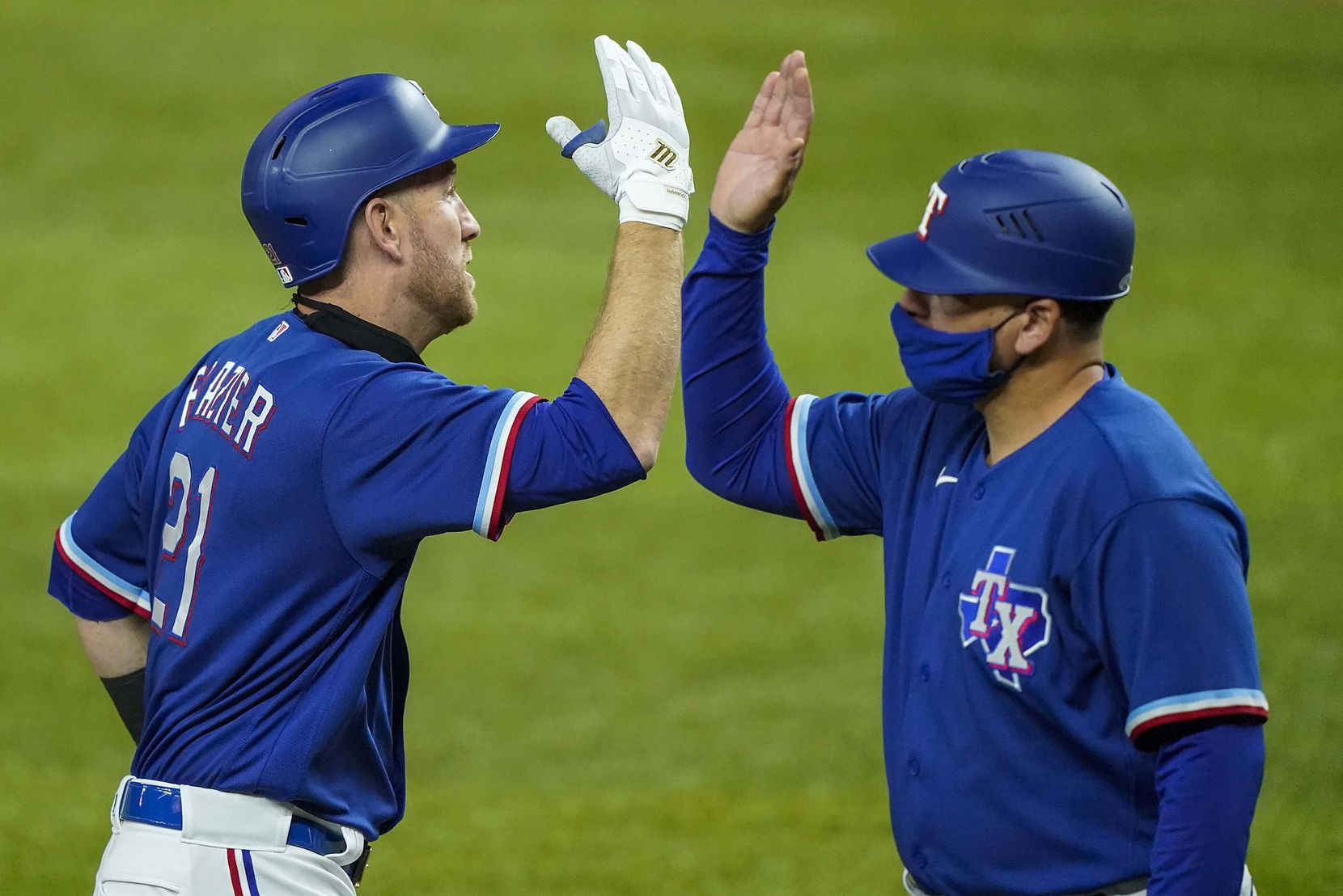 Texas Rangers first baseman Todd Frazier celebrates with coach Hector Ortiz after hitting a 3-run home run during the fifth inning of an exhibition game against the Colorado Rockies at Globe Life Field on Wednesday, July 22, 2020.