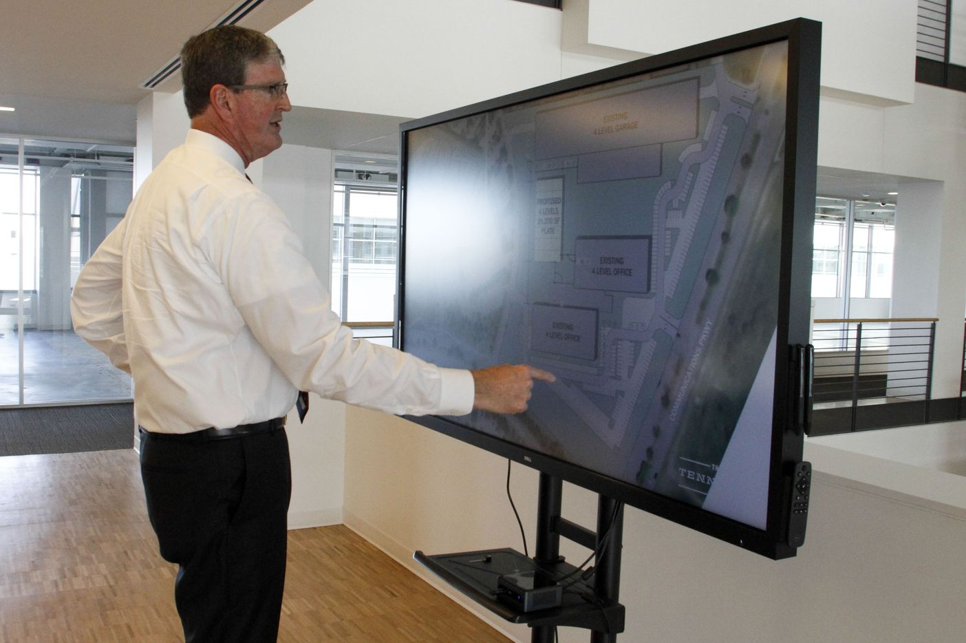 John F. Brownlee, Principal at Peloton Commercial Real Estate, points to a layout of a former Ericsson office building that Peloton is offering up for lease in Plano. (Brian Elledge/The Dallas Morning News)
