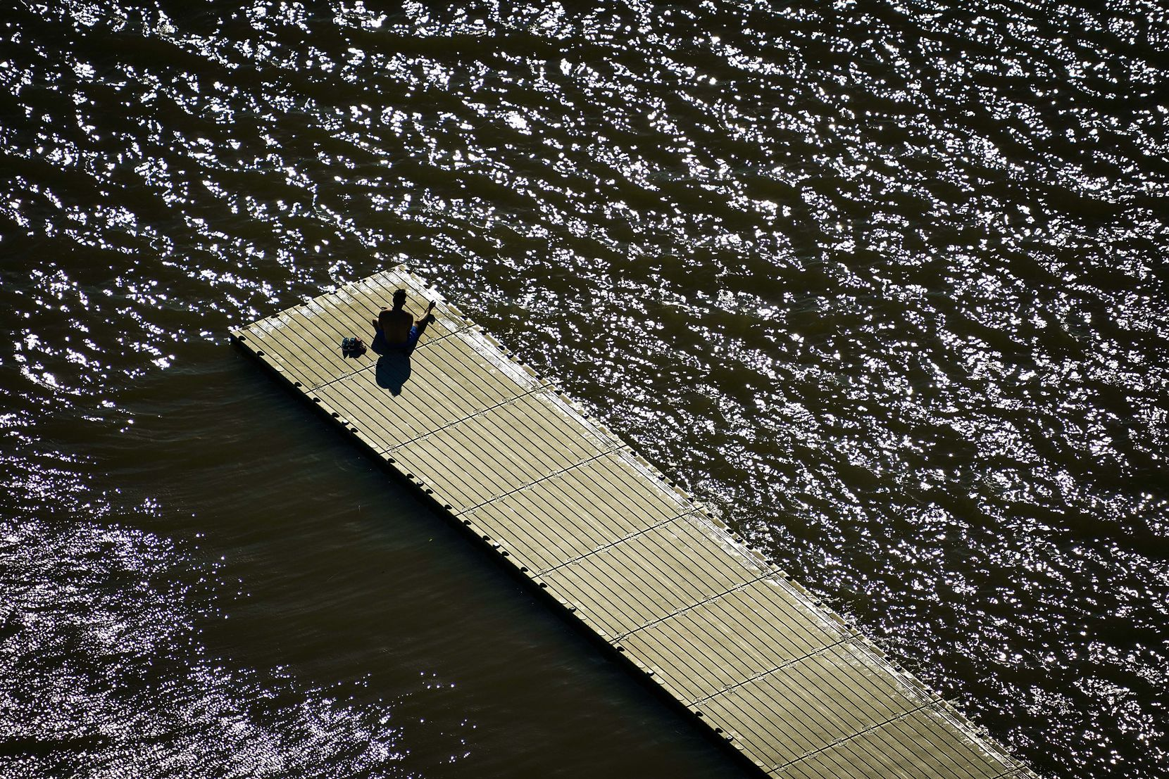 A solitary man sits on a dock at White Rock Lake in Dallas on Tuesday, March 24, 2020.