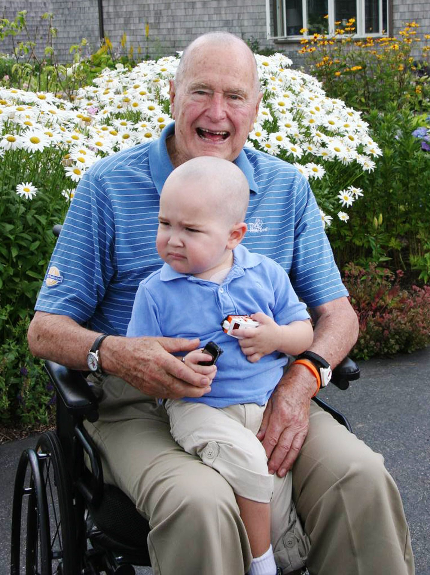 2013: President George H. W. Bush poses for a photo with his young friend Patrick (last name withheld at family's request), 2, in Kennebunkport, Maine. The former president joined members of his Secret Service detail in shaving his head to show solidarity for Patrick, who is the son of one of the agents. The child was undergoing treatment for leukemia and losing his hair as a result.