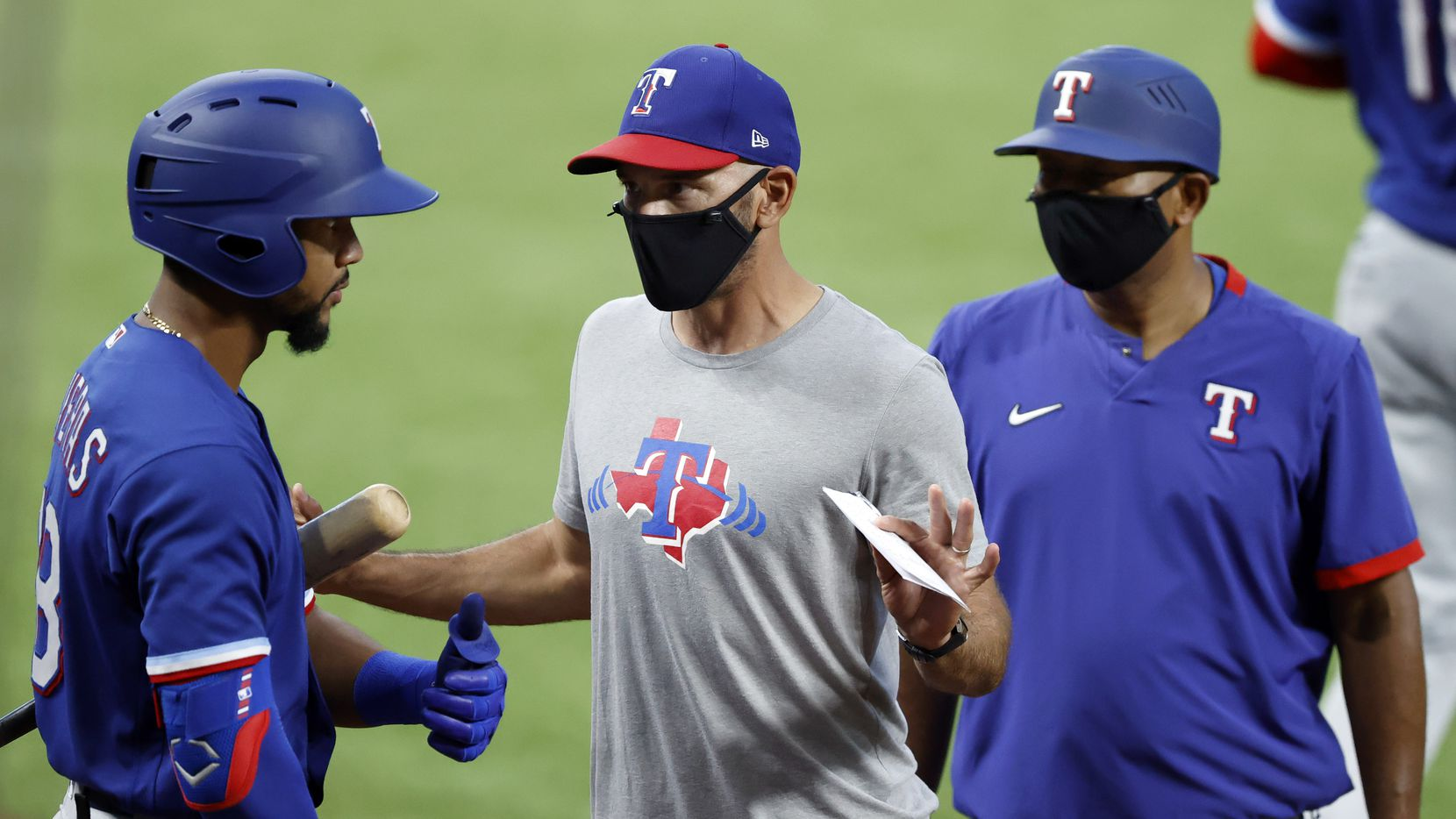Texas Rangers manager Chris Woodward (middle) wears a mask as he visits with outfielder Leody Taveras during a simulated Summer Camp game inside Globe Life Field in Arlington, Texas, Thursday, July 9, 2020.