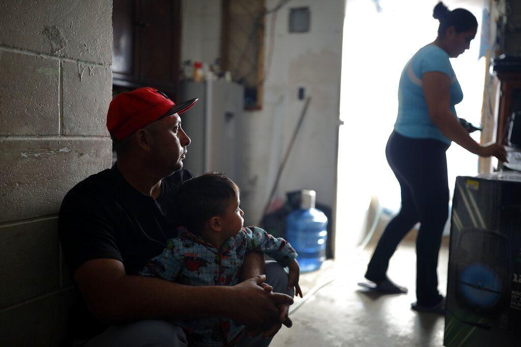 En esta fotografía de archivo del 28 de enero de 2020, los salvadoreños Juan Carlos Perla, su esposa Ruth Aracely Monroy y el hijo de ambos permanecen en una casa en las afueras de Tijuana México, tras huir de la violencia en su país en busca de asilo en Estados Unidos.