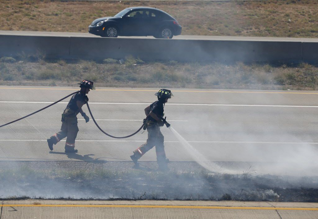 Irving firefighters battle a string of grass fires on the west side of Highway 161 sourth of Walnut Hill Lane in Irving on Sept. 8, 2015. Traffic was affected because of low visibility. (Michael Ainsworth/The Dallas Morning News)