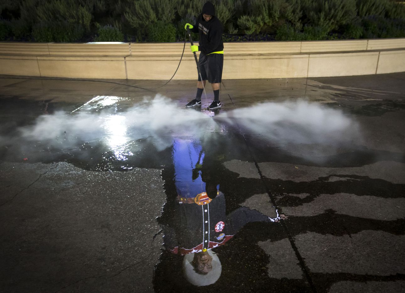 """Francisco Gallardo, 29, pressure washes the pavement in Big Tex circle in the early morning hours of Oct. 11. He said he spends two to three hours washing off """"gum, mustard, ketchup, Coke, beer ..."""""""