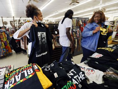 Shop owner Akwete Tyehimba (left) shows a new George Floyd 'I Can't Breathe' T-shirt to Bridget Gurly at Pan-African Connection in Dallas, Thursday, July 2, 2020.  (Tom Fox/The Dallas Morning News)