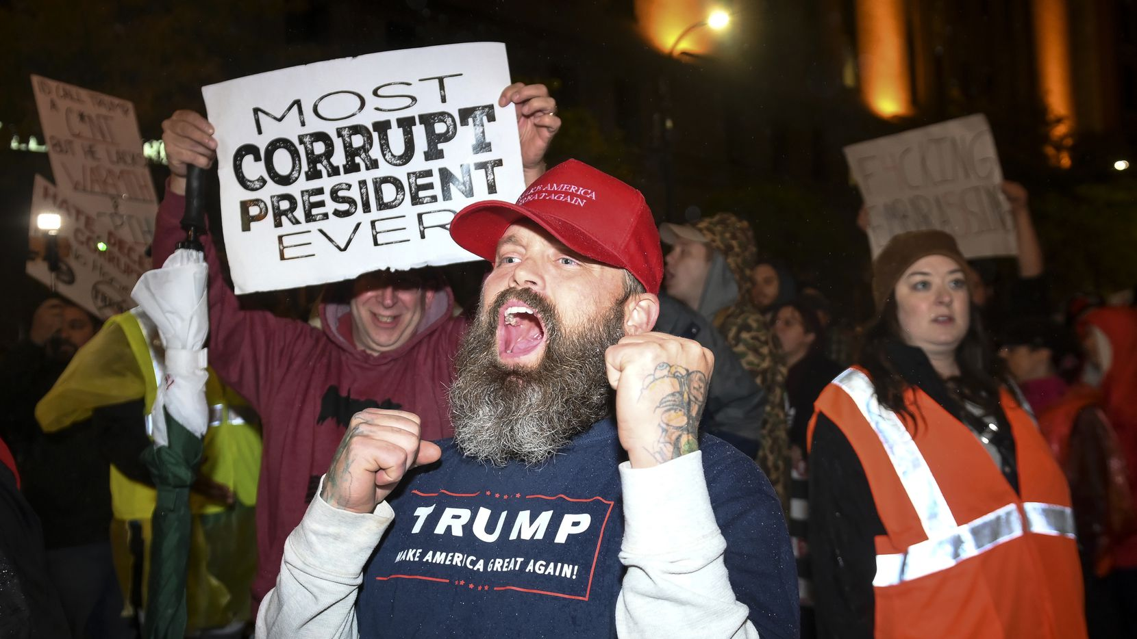 """A Trump supporter chanted """"Trump 2020"""" while making his way through crowd of anti-Trump protesters Thursday night, Oct. 10, 2019, in Minneapolis. President Donald Trump held a campaign rally Thursday at the Target Center. (Aaron Lavinsky/Star Tribune via AP)"""