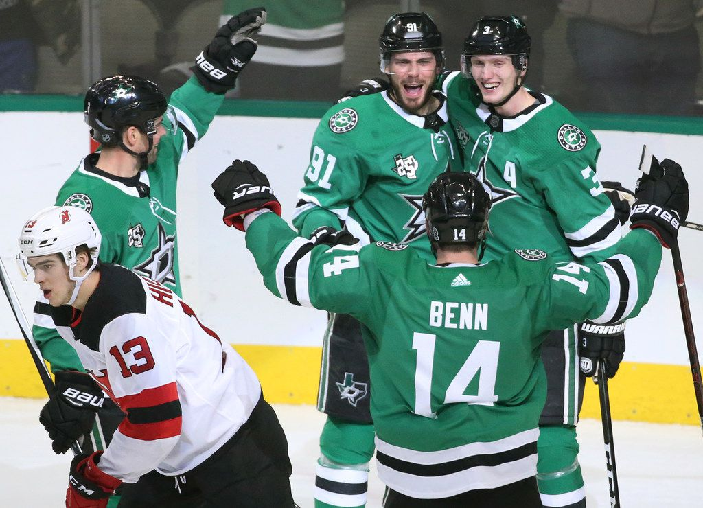 Dallas Stars Tyler Seguin (91), John Klingberg (3)  and  Jamie Benn (14) celebrate Seguin's goal in the second period as New Jersey Devils Nico Hischier (13) skates past during the New Jersey Devils vs. the Dallas Stars NHL hockey game at the American Airlines Center in Dallas on Thursday, January 4, 2018. (Louis DeLuca/The Dallas Morning News)