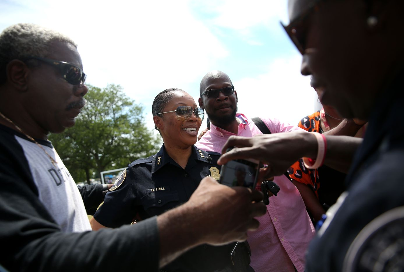 Community members pass a phone to take photos of themselves with Detroit Deputy Chief and newly named Dallas Police Chief Hall.
