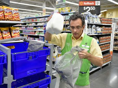 Wille Pierson, placing milk into a bin, prepares a customer's order for pick-up at the Walmart Neighborhood Market. Thursday, September 14, 2017, in Denton, Texas. (Jeff Woo/DRC)