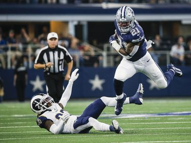 Dallas Cowboys running back Ezekiel Elliott (21) makes a leap over Los Angeles Rams defensive back Nickell Robey-Coleman (23) during the first half of an NFL matchup between the Dallas Cowboys and the Los Angeles Rams on Sunday, Dec. 15, 2019 at AT&T Stadium in Arlington, Texas. (Ryan Michalesko/The Dallas Morning News)