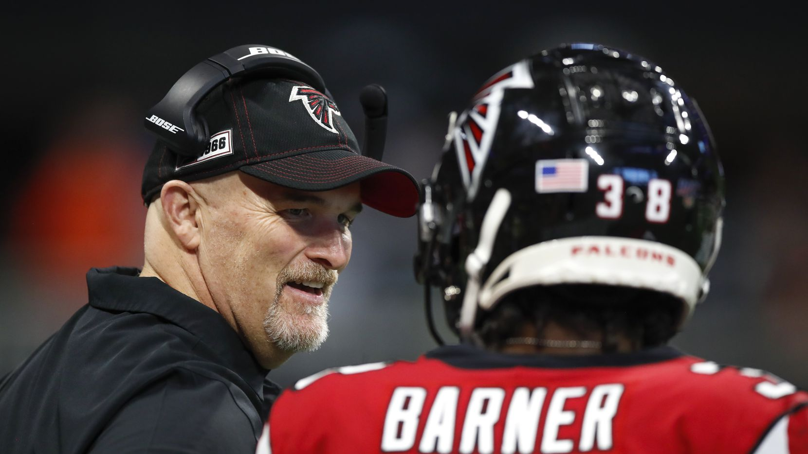 Head coach Dan Quinn of the Atlanta Falcons speaks with Kenjon Barner #38 in the second half on an NFL game against the Carolina Panthers at Mercedes-Benz Stadium on December 8, 2019 in Atlanta, Georgia