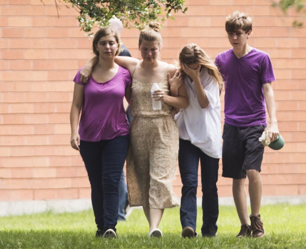 Students are emotional as they gather by the Barnett Intermediate School where parents gathered to pick up their children following a shooting at Santa Fe High School.