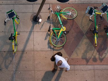A pedestrian walks around a fallen rental bike at the corner of Harwood and Elm Streets in downtown Dallas.