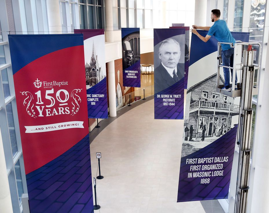 Building technician Micah Lynch hangs banners along an indoor walkway in advance of First Baptist Dallas' 150th anniversary celebration.