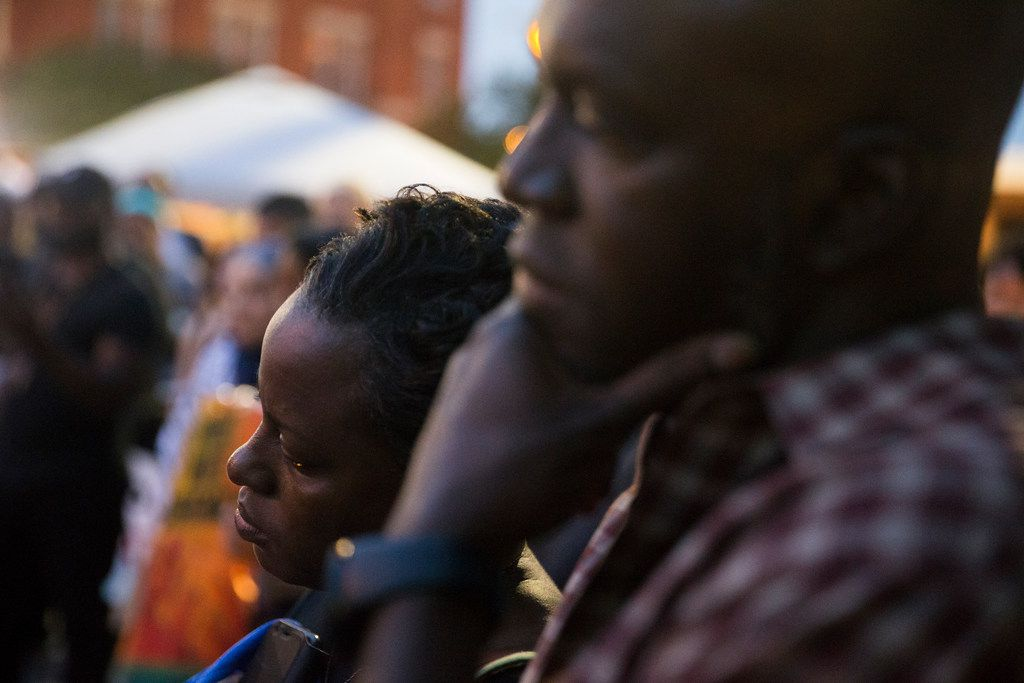 Dane Felicien listens along with his wife, Tracia,, before speaking about their family friend Botham Shem Jean during a Mothers Against Police Brutality candlelight vigil for Jean at the Jack Evans Police Headquarters on Friday, September 7, 2018 in Dallas. He was shot by a Dallas police officer who mistook his apartment for hers on Thursday night. (Shaban Athuman/ The Dallas Morning News)   ORG XMIT: 20041716A