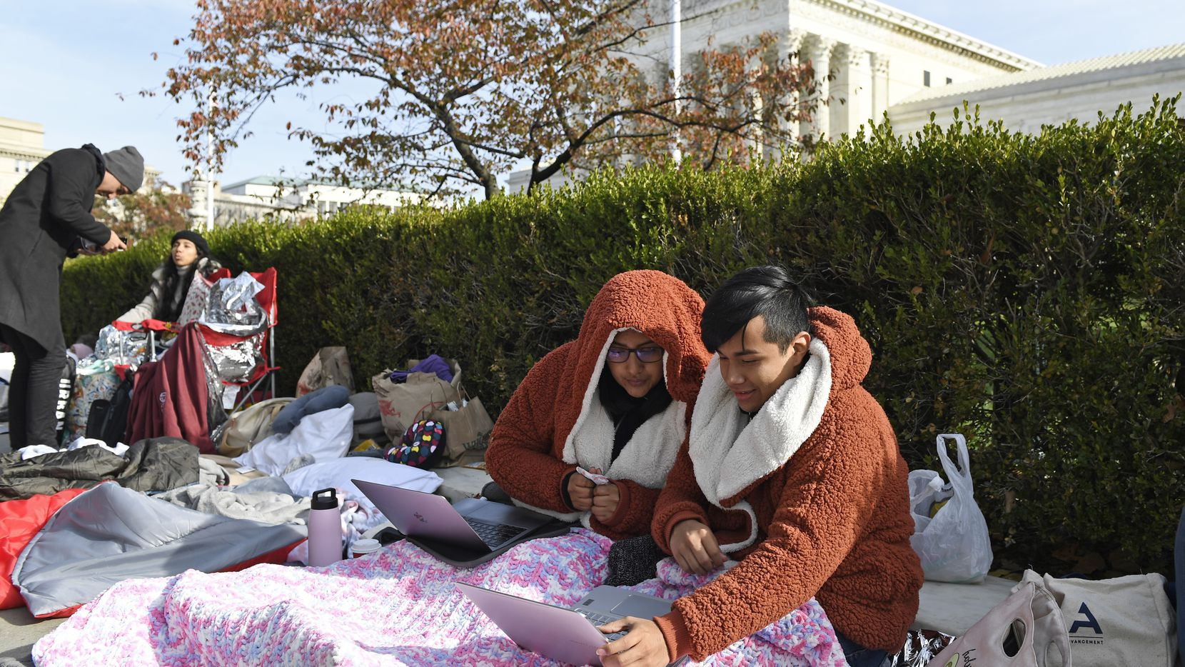 Monica Sibri, left, who is originally from Ecuador and now lives in New York, sits next to Diego Tum-Monge of Grand Island, Neb., right as they wait in line outside the Supreme Court in Washington, Monday, Nov. 11, 2019, to be able to attend oral arguments Tuesday in the case of President Trump's decision to end the Obama-era, Deferred Action for Childhood Arrivals program.