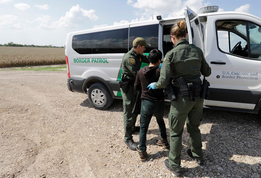 In this June 25, 2018 file photo, U.S. Border Patrol agents load a migrant from Guatemala into a van after he was caught trying to enter the United States illegally in Hidalgo.