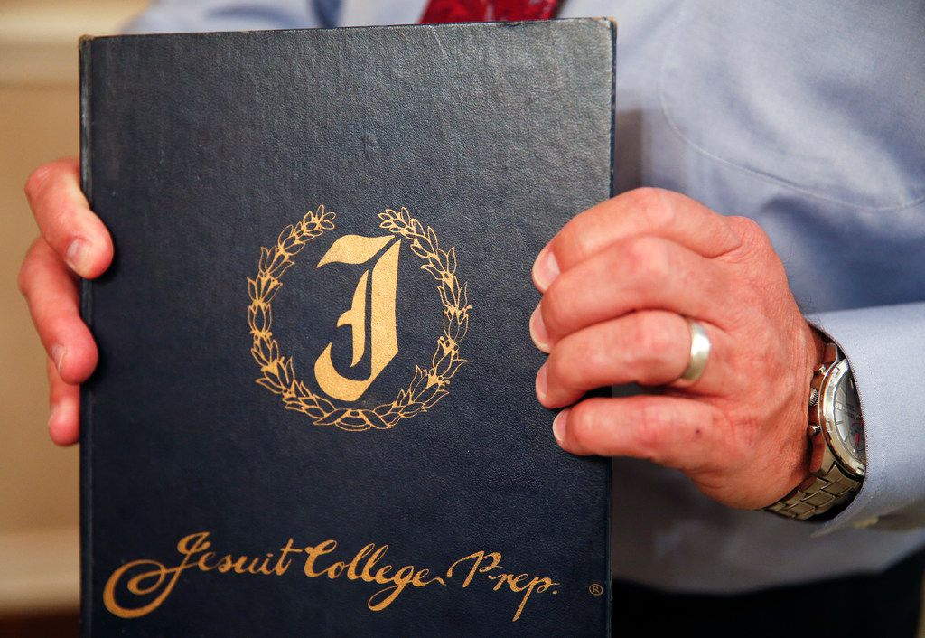 Mike Pedevilla, who is suing Jesuit prep saying priest and former president of the school Patrick Koch sexually abused him while he was a student there, holds out his 1979 Jesuit prep yearbook at his Grapevine, Texas home Wednesday, Sept. 11, 2019.