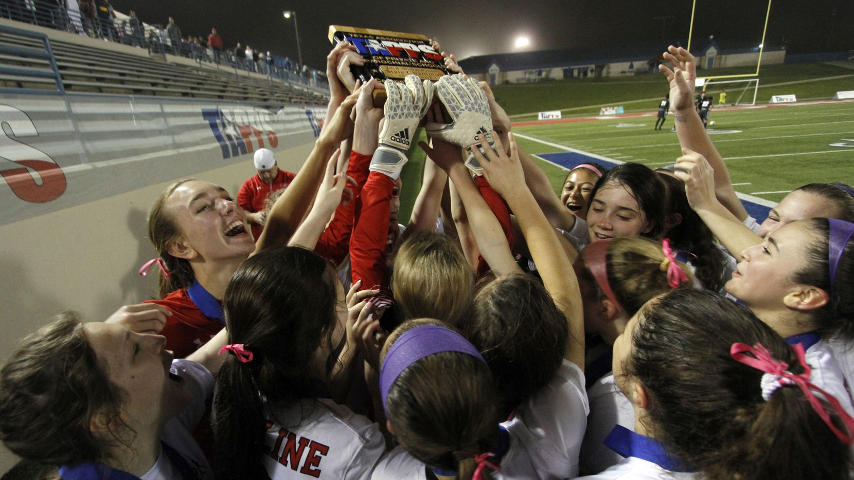 File photo, 2018: Ursuline players stretch to reach the state championship trophy they were awarded following their 2-0 victory over John Paul ll. The two teams played their TAPPS Division 1 girls state soccer championship game at Waco ISD Stadium.