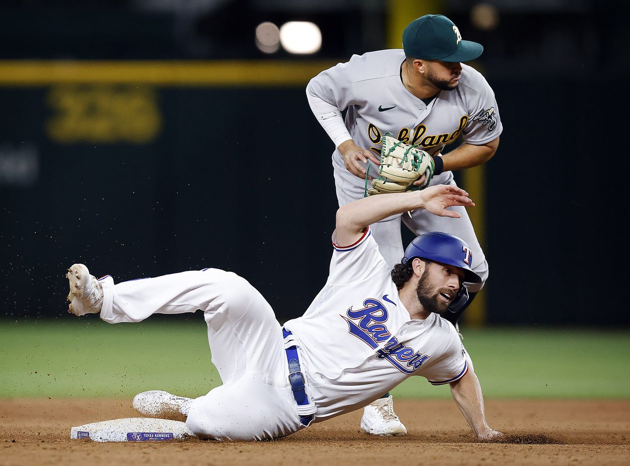 Texas Rangers Charlie Culberson (2) slides out after being tagged by Oakland Athletics second baseman Jed Lowrie (8) on a batted ball to second during the ninth inning at Globe Life Field in Arlington, Saturday, August 14, 2021.(Tom Fox/The Dallas Morning News)