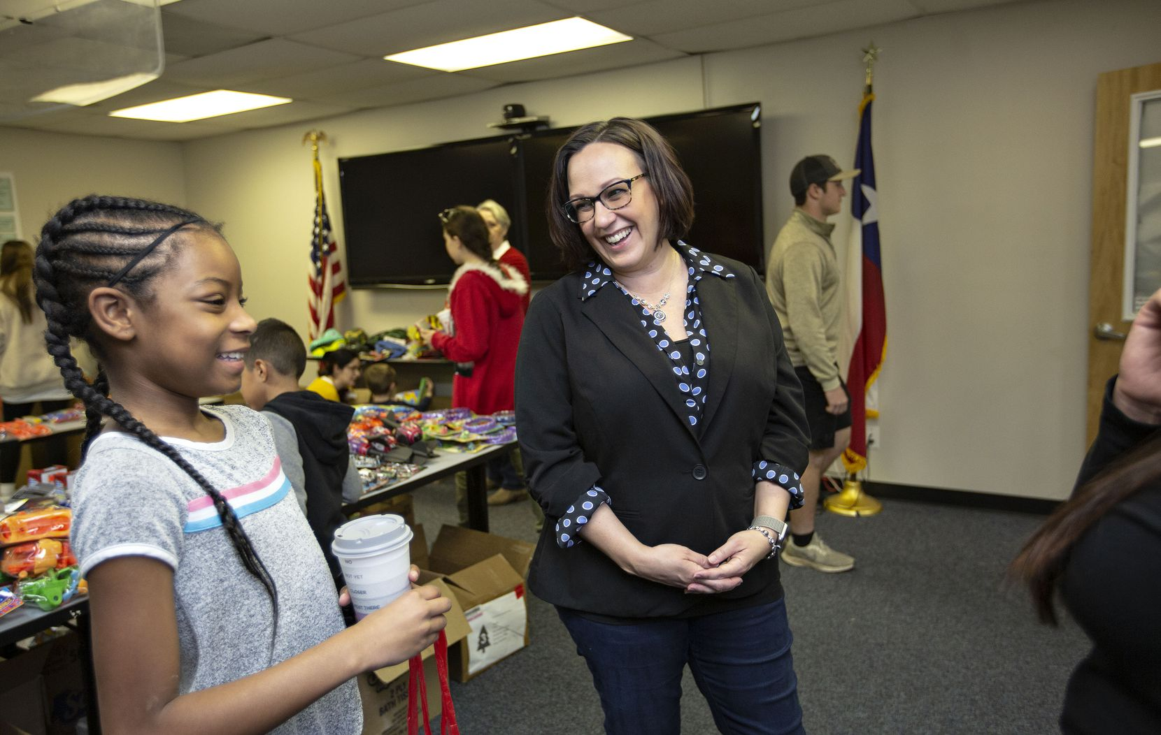 MJ Hegar chats with Azaria Jordan, 9, and her stepmother, Staff Sgt. Selina Robinson, during her visit to Operation Homefront's toy distribution event at the Army base in Austin.
