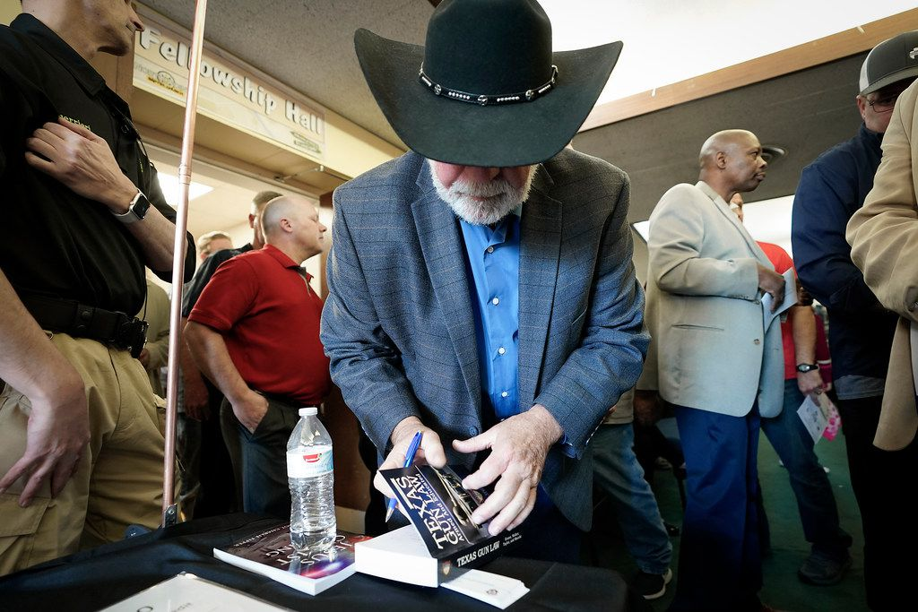 Jack Wilson, the head of the West Freeway Church of Christ volunteer security team who stopped a gunman at the church in White Settlement, autographs a copy of the book 'Texas Gun Law: Armed And Educated' during a church safety seminar at North Pointe Baptist Church on Sunday, Jan. 26, 2020, in Hurst, Texas.