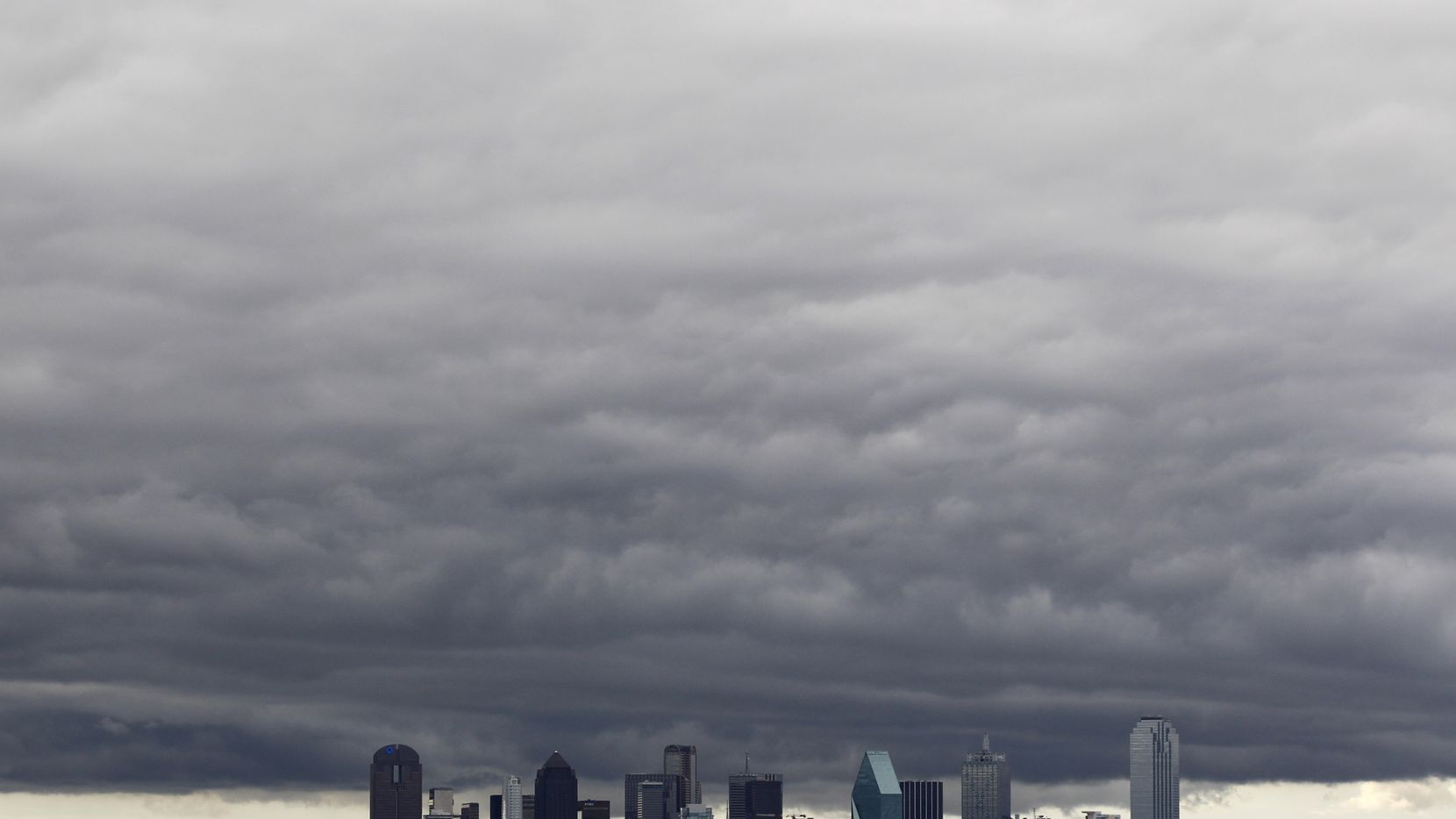 Dark clouds hang over the downtown Dallas skyline.