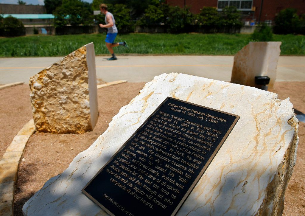 A runner on the Trinity Strand Trail passes the Circle of Heroes memorial unveiled Thursday, July 6, 2017, on Manufacturing Street in Dallas. This plaque is dedicated to Officer Patrick Zamarripa.