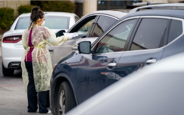 Office manager Kristy Castillo talks with a patient as cars line up for drive-thru coronavirus testing at Neighborhood Medical Center on Monday, March 16, 2020, in Dallas. Patients first were tested for flu and streptococcal infections at the center. (Smiley N. Pool/The Dallas Morning News)