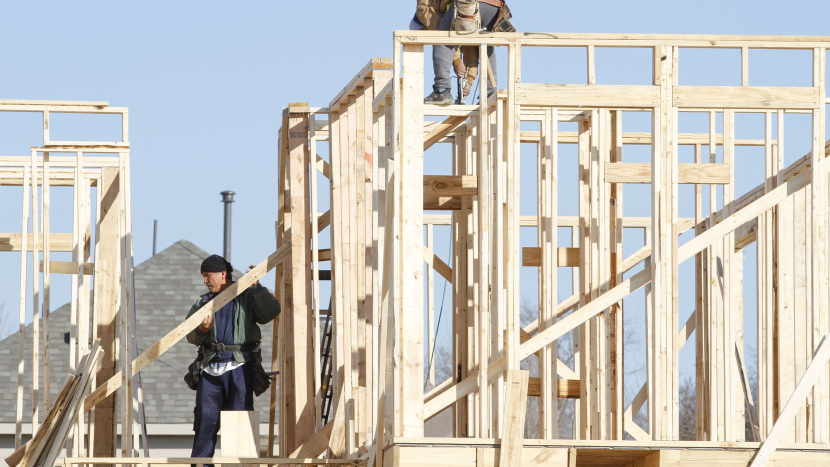 Workers frame a house under construction on Shasta Daisy Rd. in The Grove neighborhood in Frisco. Garland is encouraging owners of older homes to reinvest in their properties with a new program that provides a cash rebate for certain exterior home improvements.