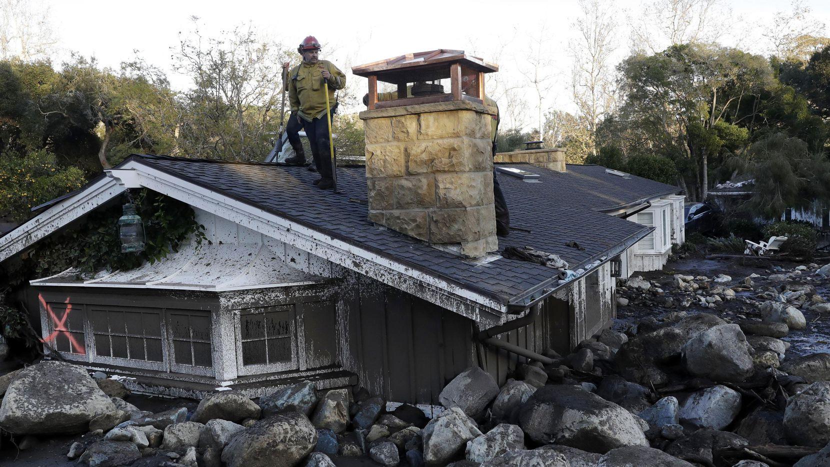 Un agente del equipo de rescate se para encima de una vivienda que fue arrollada por una alud de lodo en Montecito, California. (AP/Marcio Jose Sanchez)