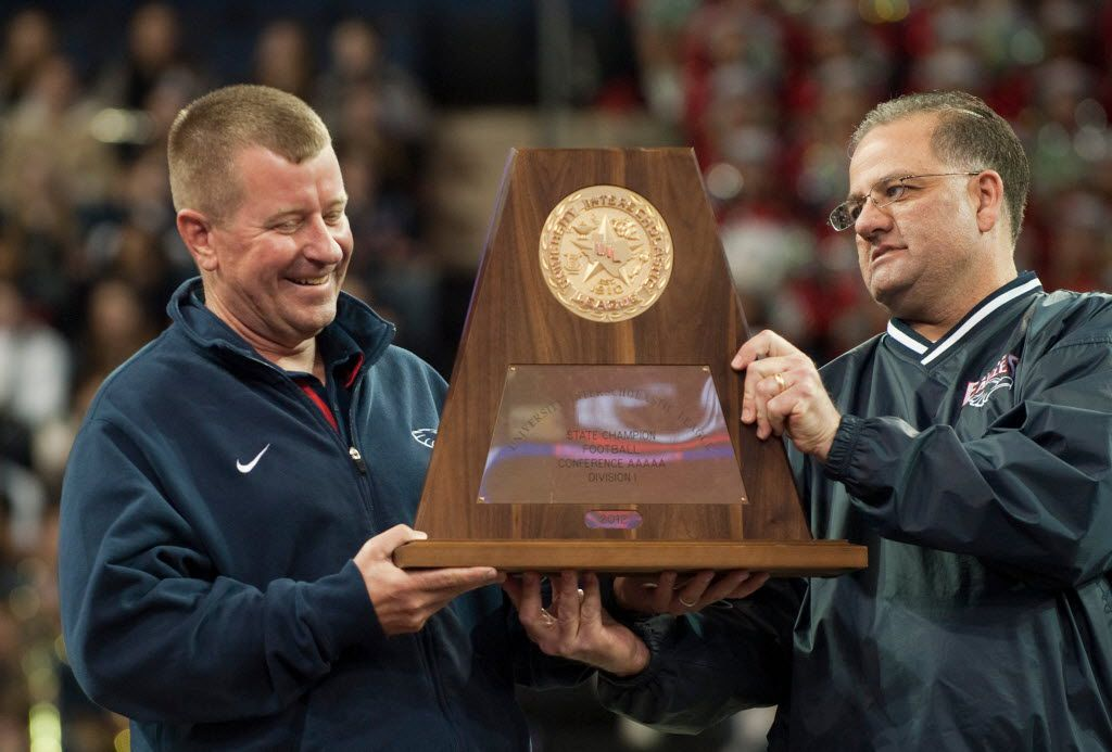 Head coach Tom Westerberg receives the UIL 5A state championship trophy from Allen ISD board of trustees Mark Jones during Allen High School's football state championship community celebration at the Allen Event Center on Wednesday, January 30, 2013 in Allen, Texas. (Cooper Neill/The Dallas Morning News)