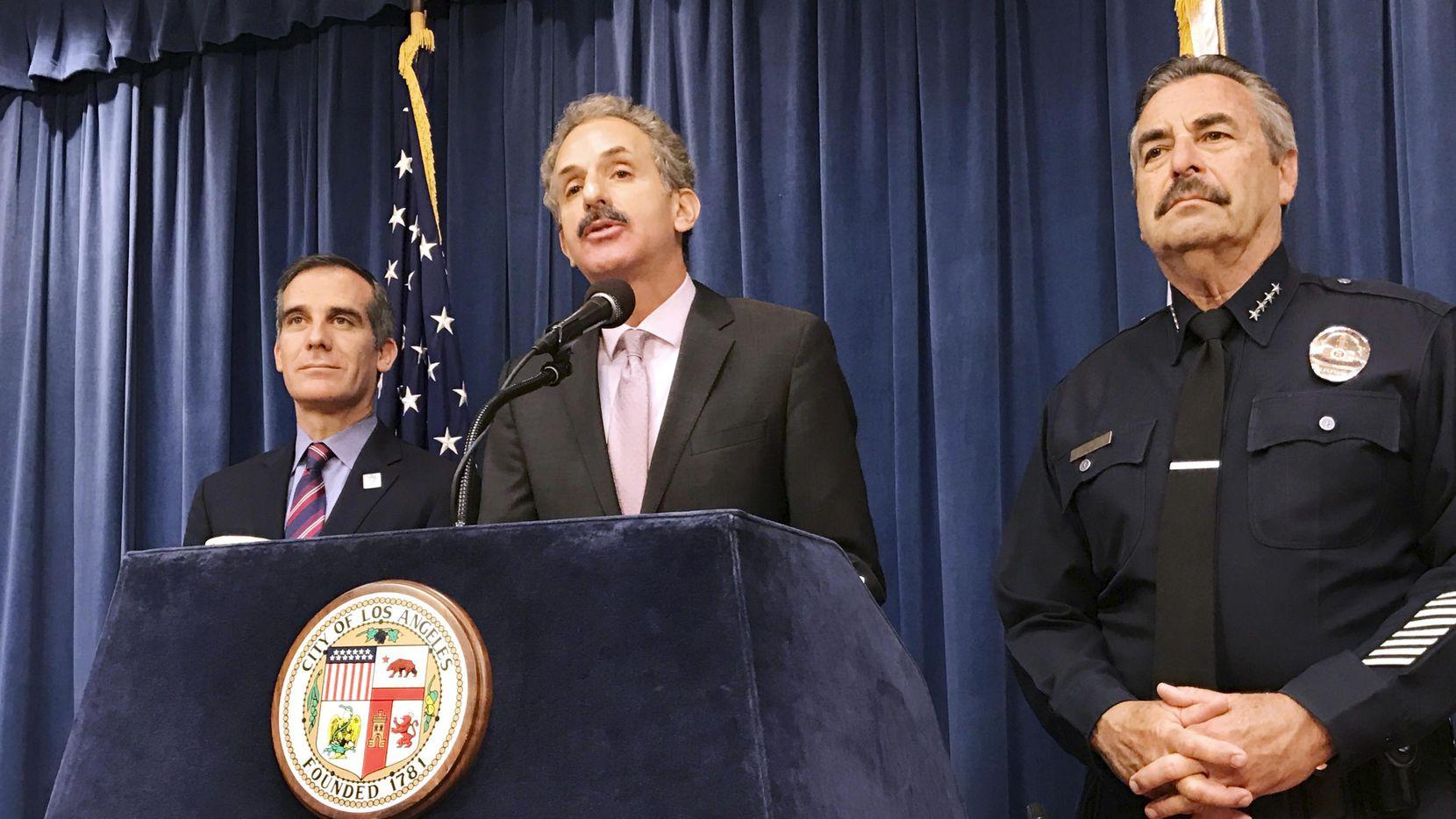 El abogado de la ciudad de Los Angeles (centro) es acompañado por el jefe de la policía Charlie Beck y el alcalde Eric Garcetti, al comentar sobre el fallo de la corte federal sobre la cooperación entre ciudades y autoridades migratorias.(AP)