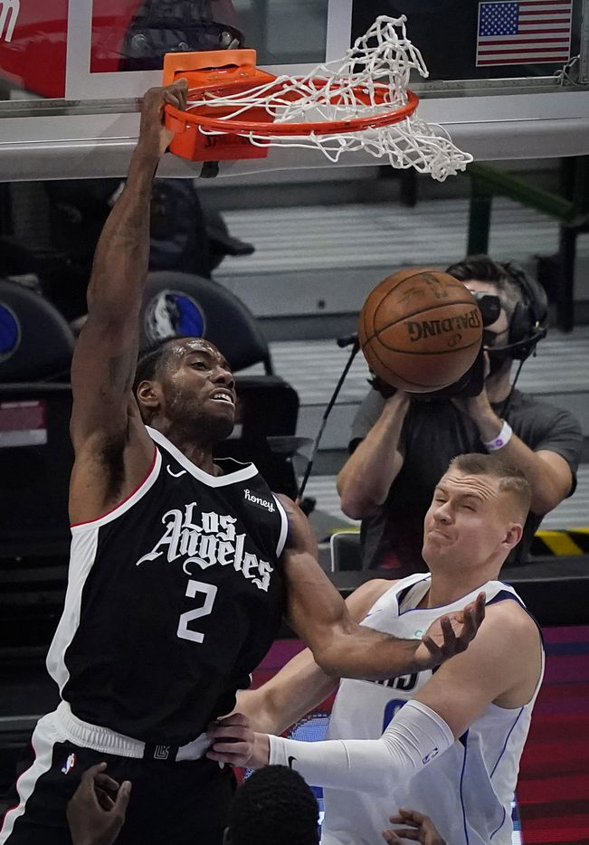 LA Clippers forward Kawhi Leonard (2) dunks the ball over Dallas Mavericks center Kristaps Porzingis (6) during the second quarter of an NBA playoff basketball game at American Airlines Center on Sunday, May 30, 2021, in Dallas.