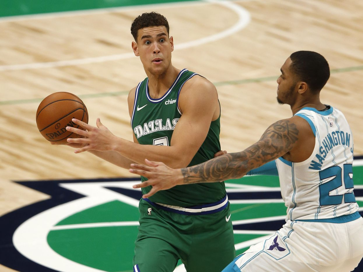 Dallas Mavericks center Dwight Powell (7) looks to pass as he is defended by Charlotte Hornets forward P.J. Washington (25) during the second quarter of play in the home opener at American Airlines Center on Wednesday, December 30, 2020 in Dallas. (Vernon Bryant/The Dallas Morning News)