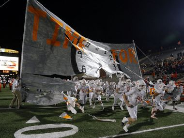 (TXHSFB) The Celina High Bobcats runs through a huge banner before the start of   a high school football playoff game against Gilmer High on Friday, December 11, 2014. (John F. Rhodes / Special Contributor)