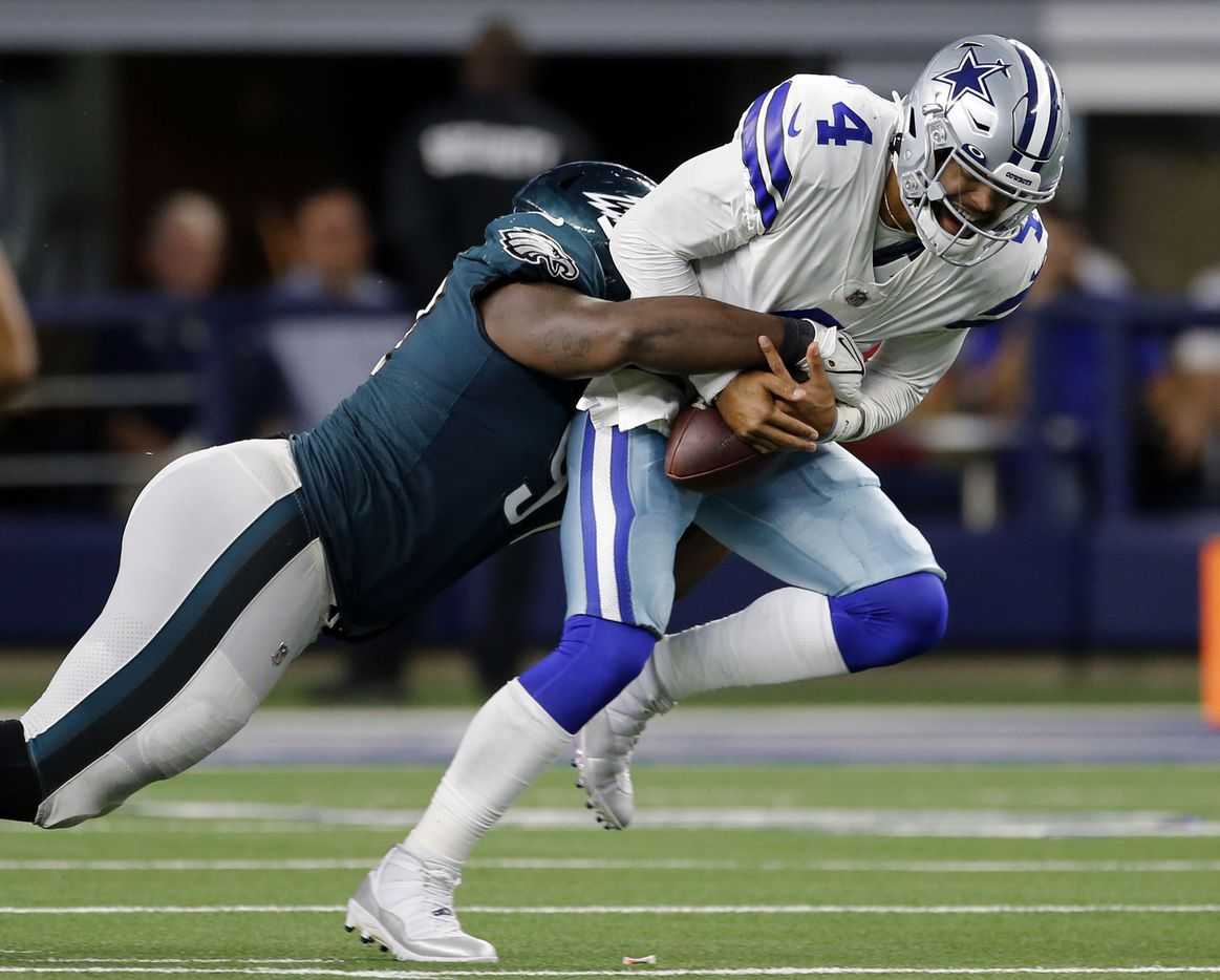 Dallas Cowboys quarterback Dak Prescott (4), right, hangs onto the football after being hit by Philadelphia Eagles nose tackle Javon Hargrave (97) during the second half of a NFL football game between the Dallas Cowboys and the Philadelphia Eagles High at AT&T Stadium in Arlington on Monday, September 27, 2021. (John F. Rhodes / Special Contributor)