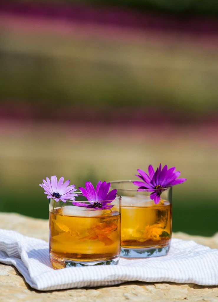 Rose Old Fashioned drinks garnished with African daisies, which are edible.