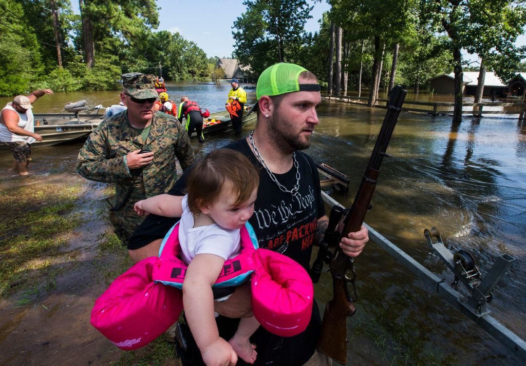 Robert Burge holds his daughter, Chevy Wayne, 1, and his rifle as Marines and members of a swift water rescue task force from Tampa, Fla., respond to victims of flooding near Lumberton.
