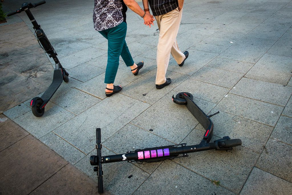 A couple walks past a pair of rental scooters littering Commerce Street in downtown Dallas on Saturday, July 13, 2019.