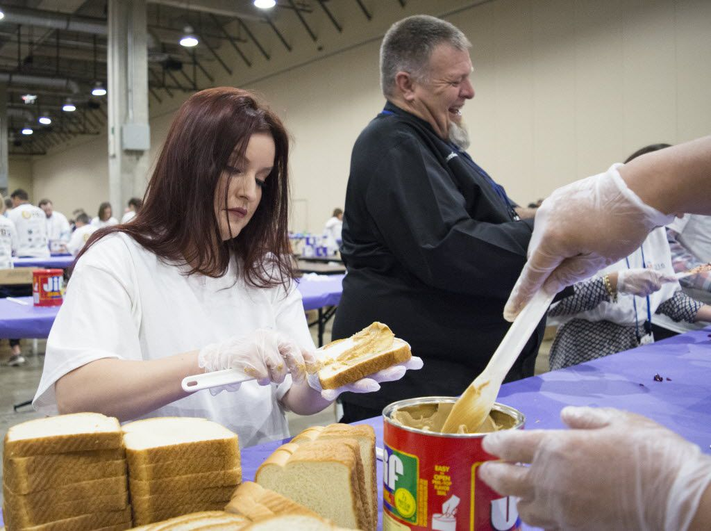 15 minutes into the Guinness World Record Spreading Party, Spread the Love volunteer Eva Amezquith spreads peanut butter onto bread before passing it off to the next volunteer to have grape jelly spread onto it.