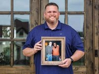 Tyler Tines Pride poses for a portrait in front of his home in Lindale as he holds a photo of himself and his father, the late country music icon Charley Pride.